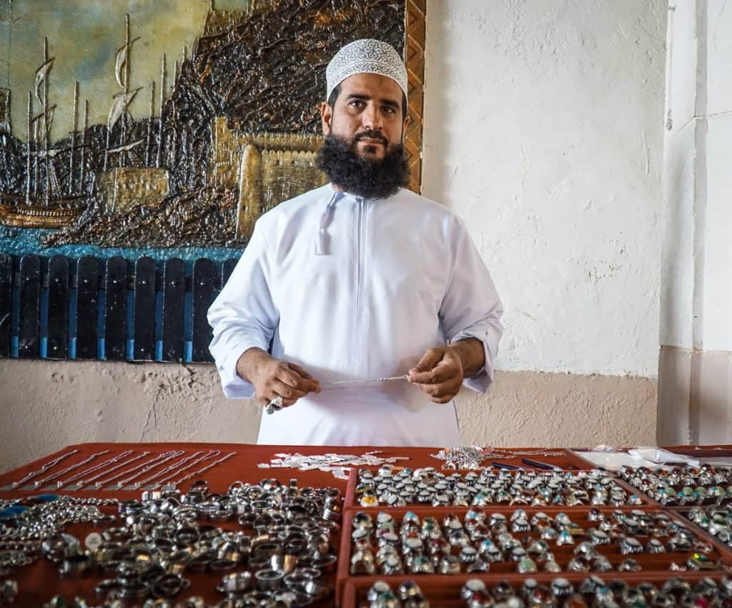 A seller shows off his jewelry at Muttrah Souk