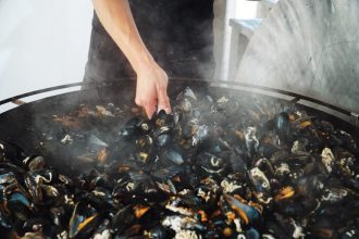 Mussels being cooked in a large pan at Musselbaren Ljungskile