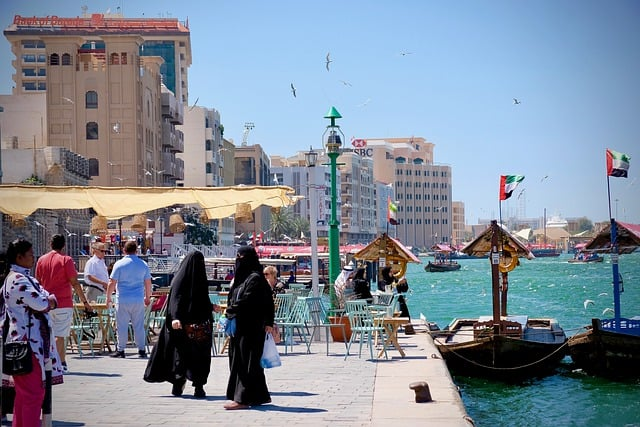 Two local women in black abayas stand by the creek in old Dubai. What To Wear in Dubai: The Ultimate Dubai Packing List tells you how to pack for Dubai, whether it's a desert safari, shopping mall, mosque, beach, or nightclub in Dubai you're going to. My tips are from the perspective of a Dubai born and raised expat along with style tips for both men and women to help you gain cultural context when you pack for Dubai.