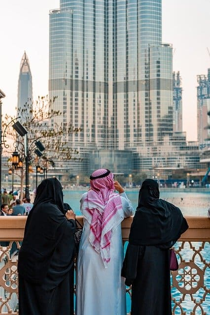 A local family in traditional dress in Dubai/ What To Wear in Dubai: The Ultimate Dubai Packing List tells you how to pack for Dubai, whether it's a desert safari, shopping mall, mosque, beach, or nightclub in Dubai you're going to. My tips are from the perspective of a Dubai born and raised expat along with style tips for both men and women to help you gain cultural context when you pack for Dubai.